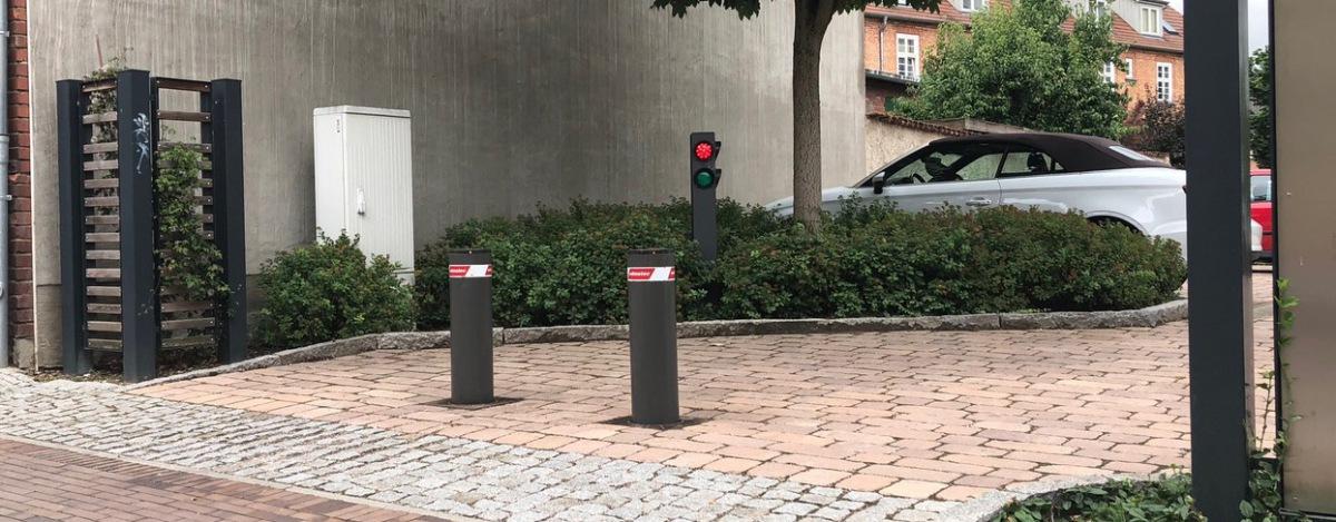 zwei graue Verkehrspoller  sperren einen Parkplatz ab
